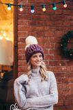 Blonde woman in purple knitted hat. S and grey sweater make posing with brick wall and Christmas garland on the background Royalty Free Stock Images