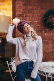 Blonde woman in purple knitted hat. S and grey sweater make posing with brick wall and Christmas garland on the background Stock Image