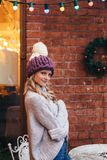 Blonde woman in purple knitted hat. S and grey sweater make posing with brick wall and Christmas garland on the background Stock Images