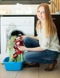 Blonde woman putting clothes in to  machine Royalty Free Stock Images