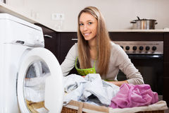 Blonde woman putting clothes in to washing machine Royalty Free Stock Photos