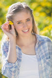 Blonde woman putting flower in hair Stock Photos
