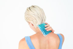 Blonde woman putting gel pack on neck Royalty Free Stock Images