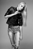 Blonde woman in ragged jeans and jacket Stock Images