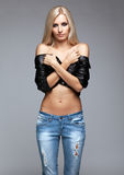 Blonde woman in ragged jeans and jacket. Blonde young woman in ragged jeans and black jacket on gray background Stock Photos