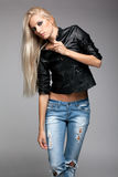Blonde woman in ragged jeans and jacket. Blonde young woman in ragged jeans and black jacket on gray background stock photography