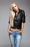 Blonde woman in ragged jeans and jacket. Blonde young woman in ragged jeans and black jacket on gray background Royalty Free Stock Photo