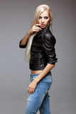 Blonde woman in ragged jeans and jacket Royalty Free Stock Photography