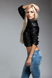 Blonde woman in ragged jeans and jacket. Blonde young woman in ragged jeans and black jacket on gray background royalty free stock photography