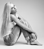 Blonde woman in ragged jeans and vest. Monochrome portrait of blonde young woman in ragged jeans and vest sitting on floor on gray background royalty free stock photo