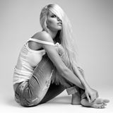 Blonde woman in ragged jeans and vest Royalty Free Stock Photography