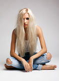 Blonde woman in ragged jeans and vest. Blonde young woman in ragged jeans and vest sitting on floor on gray background royalty free stock images