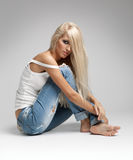 Blonde woman in ragged jeans and vest. Blonde young woman in ragged jeans and vest sitting on floor on gray background Stock Image