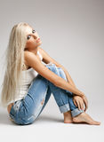 Blonde woman in ragged jeans and vest. Blonde young woman in ragged jeans and vest sitting on floor on gray background stock photos