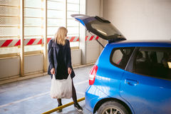 Blonde woman in raincoat and pantyhose stacks purchases from grocery store in trunk of car blue color in covered parking of sh Stock Images
