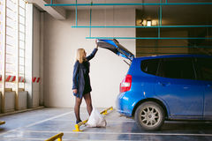 Blonde woman in raincoat and pantyhose stacks purchases from grocery store in trunk of car blue color in covered parking of sh Stock Photo