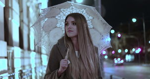 Blonde woman  a rainy day walking with the umbrella. Evening time smiling stock footage