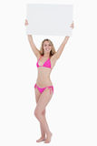 Blonde woman raising a blank poster above her head Royalty Free Stock Photos