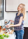 Blonde woman with raw  fish Stock Photos