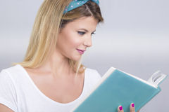 Blonde woman reading. Beautiful blonde woman reading a book, smiling Royalty Free Stock Image