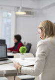 Blonde woman reading a book in the office Royalty Free Stock Images
