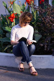 Blonde woman reading a book outside Royalty Free Stock Photography
