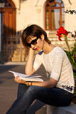 Blonde woman reading a book outside. Blonde woman with glasses reading a book outside near some flowers Royalty Free Stock Image