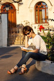 Blonde woman reading a book outside. Blonde woman with glasses reading a book outside near some flowers Royalty Free Stock Photography