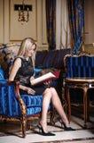 Blonde woman reading menu book Stock Photo