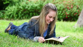 Blonde woman reading a novel. In a park stock video
