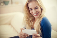 Blonde woman reading something at her smartphone Royalty Free Stock Photos