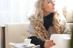 Blonde woman reading on a tablet Stock Photography