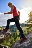 Blonde woman in red climbing boots walking on the mountains Royalty Free Stock Images