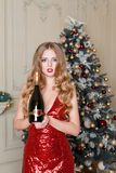 Blonde woman in red dress with bottle of white wine or champagne in luxury interior. Christmas tree, presents and gift Stock Image