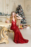 Blonde woman in red dress with glass of white wine or champagne siting on a chair in luxury interior. Christmas tree Royalty Free Stock Image