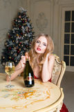 Blonde woman in red dress with glass of white wine or champagne siting on a chair in luxury interior. Christmas tree Stock Photo