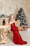 Blonde woman in red dress with glass of white wine or champagne siting on a chair in luxury interior. Christmas tree, presents and Stock Images