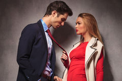 Blonde woman in red dress pulling her lover by tie Stock Image