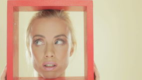Blonde woman with a red frame. Attractive blonde woman with a red frame holding it so the it surrounds her face looking upwards stock video footage