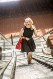 Blonde woman with red handbag posing on escalator Royalty Free Stock Images