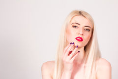Blonde woman with red lips and with a manicure touching her face. Manicure. Stock Photos