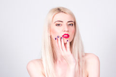 Blonde woman with red lips and with a manicure touching her face. Manicure. Royalty Free Stock Photos