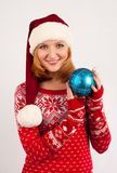 Blonde woman in red New Year`s sweater and New Year`s cap on white background holds Christmas tree ball stock images