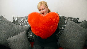 Blonde woman with red pillow heart shaped. Saint Valentine and International Women`s Day, Eight 8 March stock video