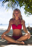 Blonde woman in red swimsuit sits at the tropical beach Stock Images