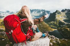Blonde woman relaxing alone with red backpack in mountains. Norway Traveling healthy lifestyle adventure concept active summer vacations exploring outdoor Stock Photo