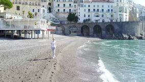 Blonde woman relaxing on the beach at the morning - Amalfi coast, Italy. stock video