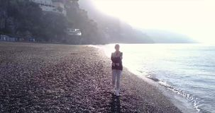 Blonde woman relaxing on the beach at the morning - Amalfi coast, Italy. stock footage