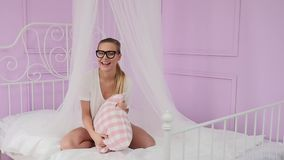 Blonde woman relaxing in bed. stock footage