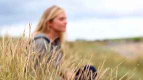 Blonde woman relaxing in the dunes stock video footage